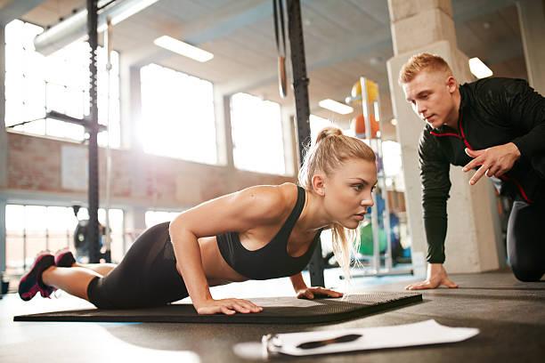 mujer ejercicio con entrenador personal en el gimnasio. - entrenador personal fotografías e imágenes de stock