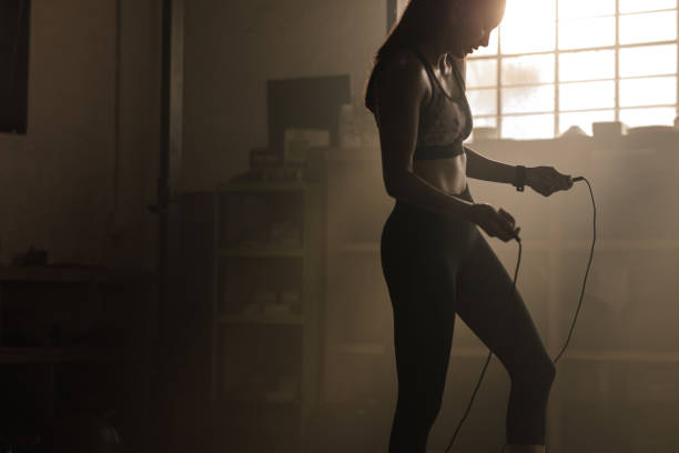 Female exercising with skipping rope at gym stock photo