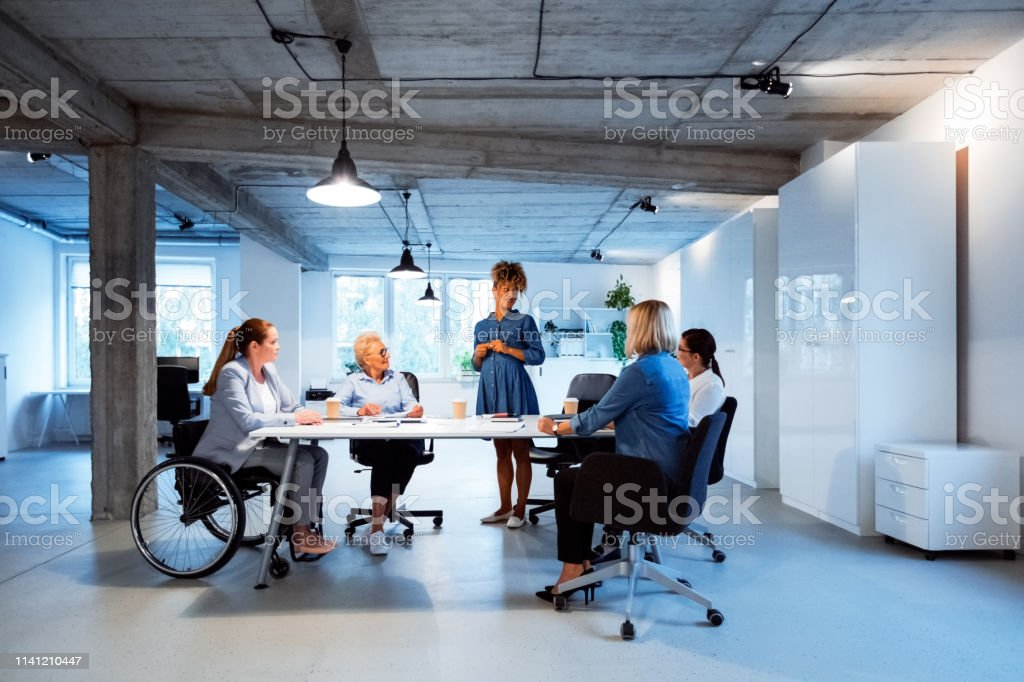 Female expertise sharing her ideas with colleagues Expertise sharing her business ideas with colleagues in new office. Female professionals are brainstorming at desk. They are working together. 35-39 Years Stock Photo