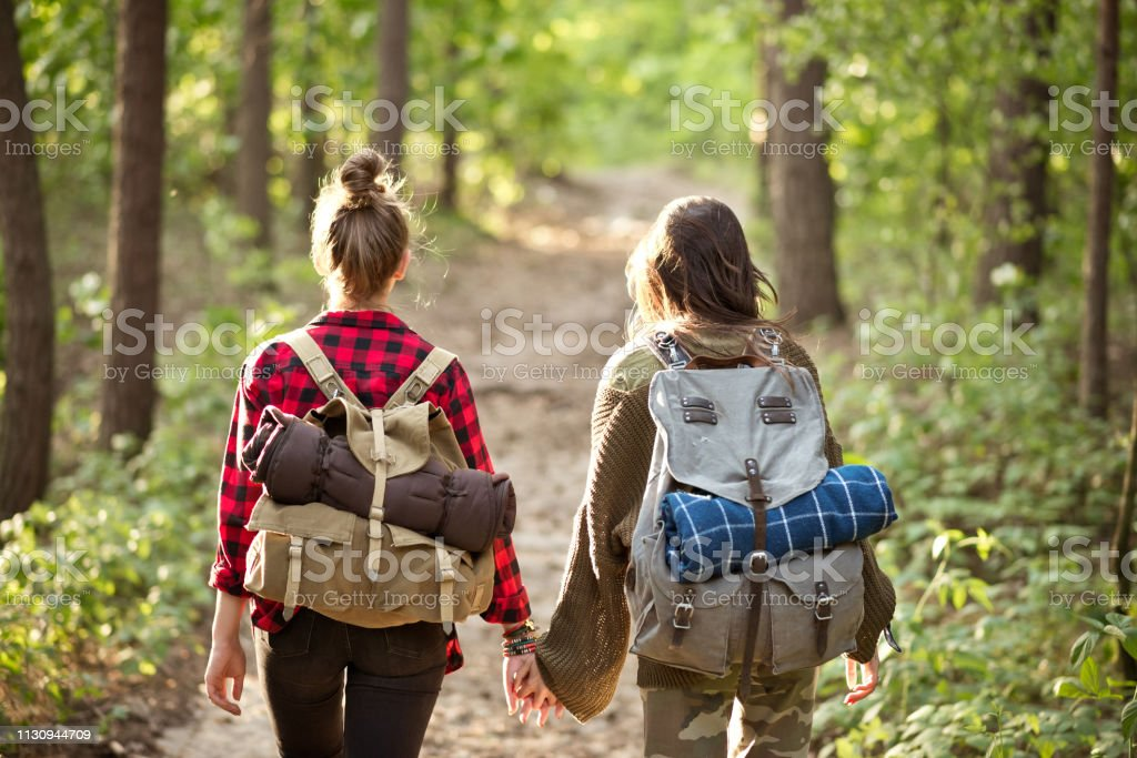 Female explorers hiking holding hands in forest Female explorers hiking holding hands in forest. Rear view of young explorers are walking with backpacks. Friends are spending weekend together. 20-24 Years Stock Photo