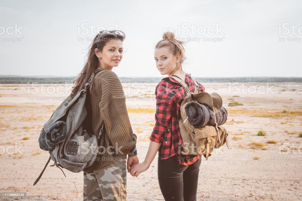 Female explorers holding hands standing in desert Portrait of beautiful young women holding hands in desert. Full length of female hikers are standing with backpacks. They are spending summer vacation together. 20-24 Years Stock Photo