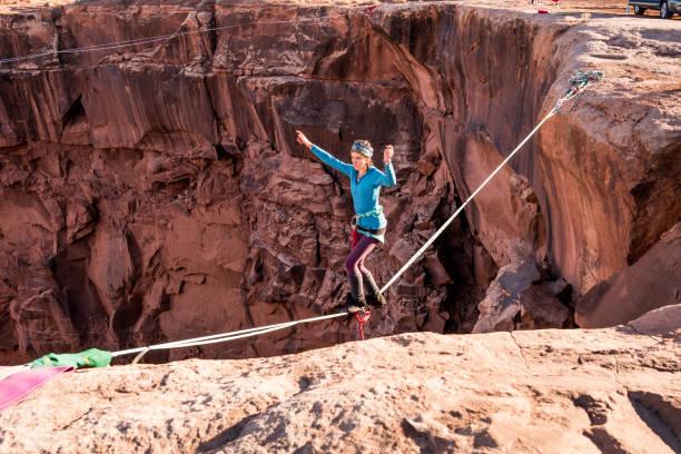 mujer highlining atleta extrema o slacklining cerca moab utah - alambre fotografías e imágenes de stock