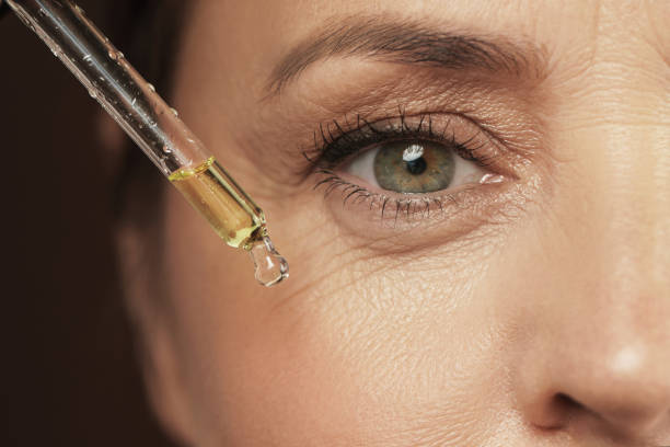 Female eye and dropper with rejuvenating serum stock photo