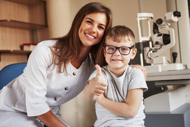 Weiblicher Augenarzt sitzt mit dem Kind nach dem Sehtest – Foto