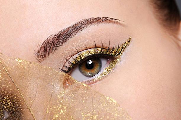 weibliche auge mit einem goldenen pfeil-make-up - goldenes augen make up stock-fotos und bilder