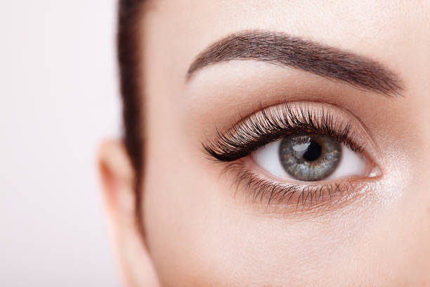 female eye with long false eyelashes - eye stock pictures, royalty-free photos & images