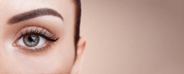 female eye with long false eyelashes - eye imagens e fotografias de stock