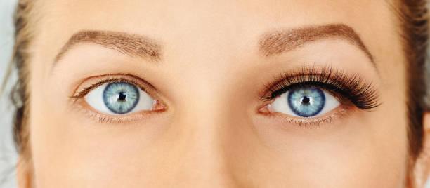 Female eyes with long false eyelashes, befor and after change Eyelash extensions, make-up, cosmetics concept. Close up false eyelash stock pictures, royalty-free photos & images