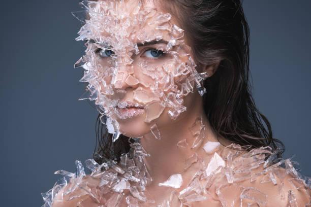 weibliches gesicht mit viel kleine stücke aus glas oder eis bedeckt - königin kopfteil stock-fotos und bilder
