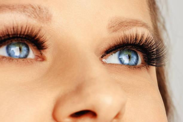 face fêmea com olhos azuis com as pestanas falsas longas - olhos azuis - fotografias e filmes do acervo