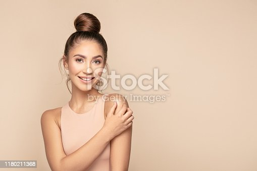 Beauty feminine portrait of female face with healthy natural skin. Beautiful tanned girl with brown hair looking at camera. Pretty attractive young woman posing at studio on beige studio background.