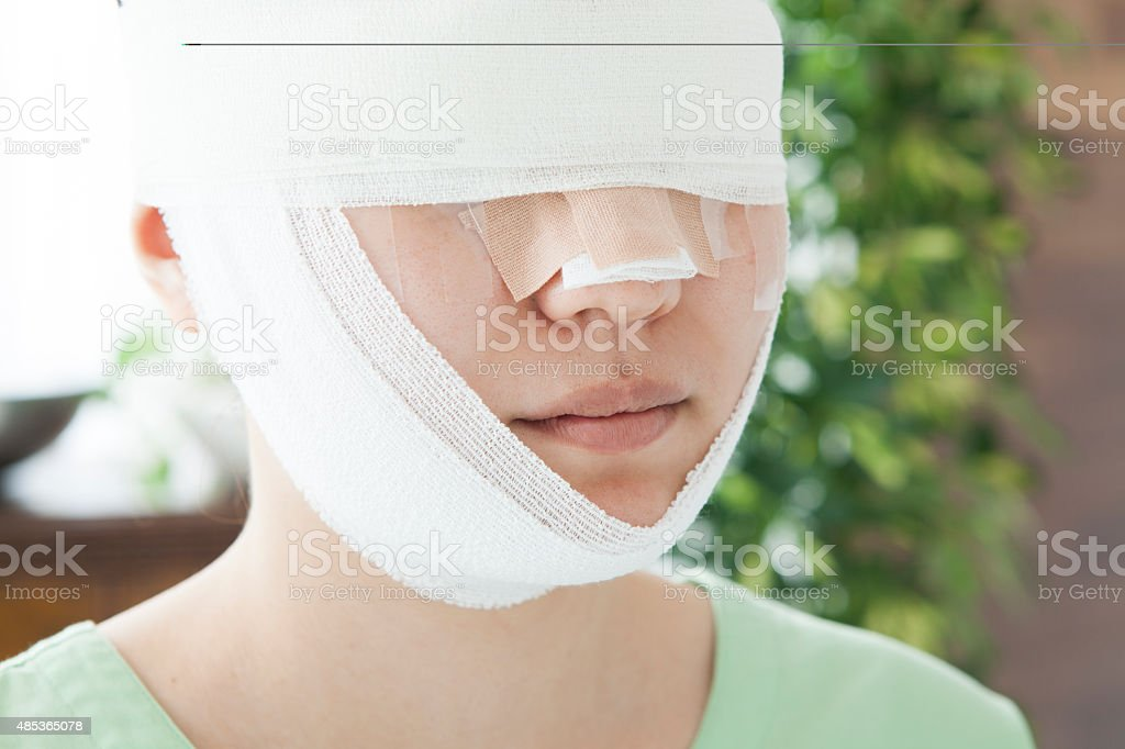 Female face wrapped in bandages