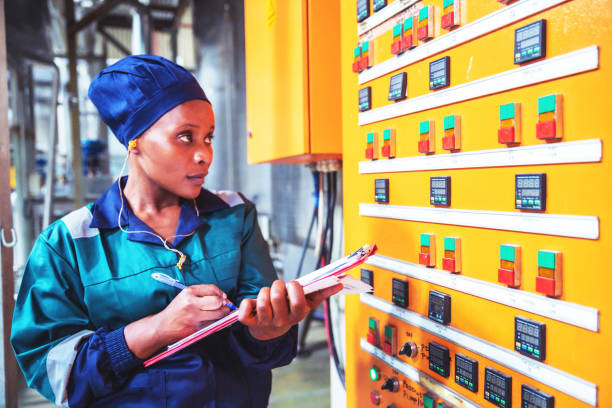 Female Factory Engineer Checking the Electrical Panel stock photo