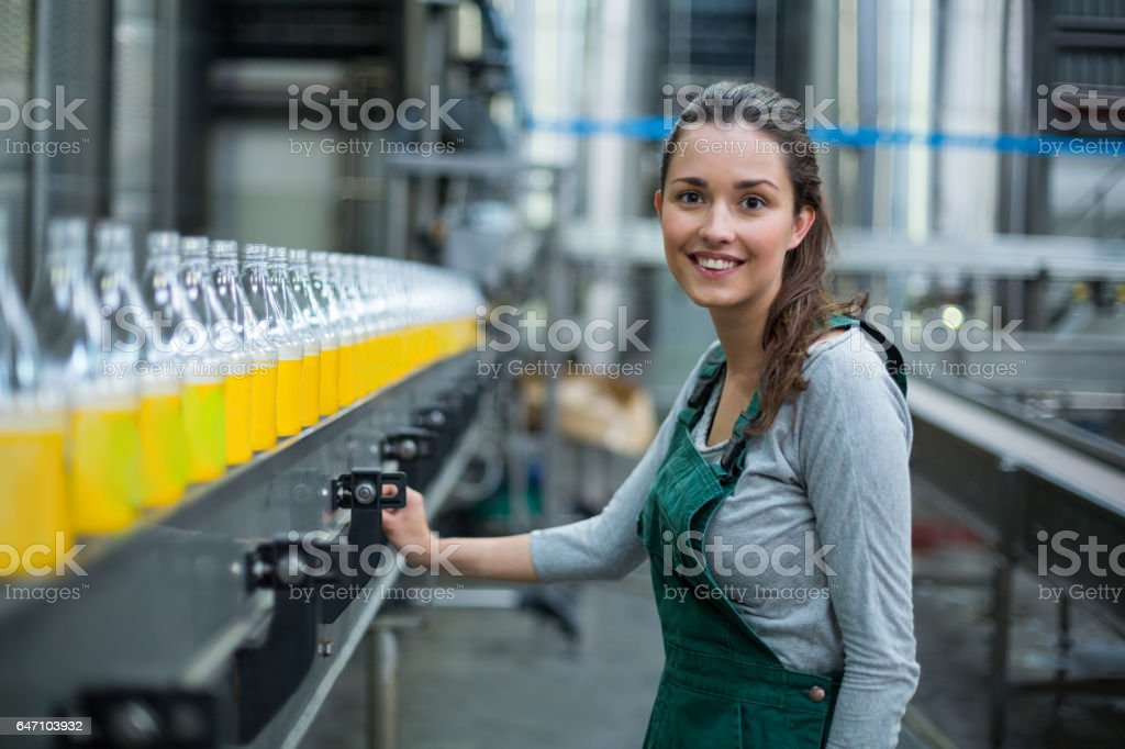 Female factory worker standing near production line stock photo