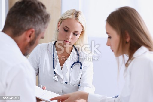 istock Female family doctor listen carefully young couple 863134054