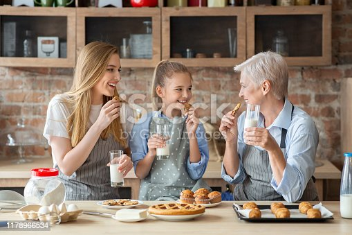 Happy female family enjoying fresh domestic pastry, drinking milk and talking, copy space
