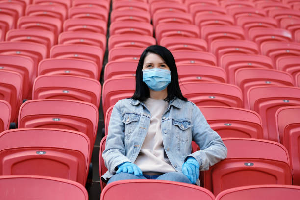 A female fan in a medical mask and rubber gloves sits alone in an empty stadium with red seats. Cancellation of sporting events during the coronavirus. One man army concept. A female fan in a medical mask and rubber gloves sits alone in an empty stadium with red seats. Cancellation of sporting events during the coronavirus. One man army concept. football fans stock pictures, royalty-free photos & images