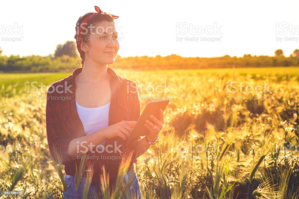Agricultrice, debout dans un champ avec tablette et en examinant les cultures. - Photo