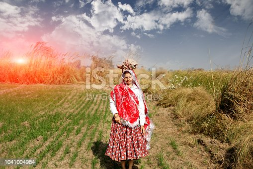 Female farmer standing portrait near wheat crop field during springtime.