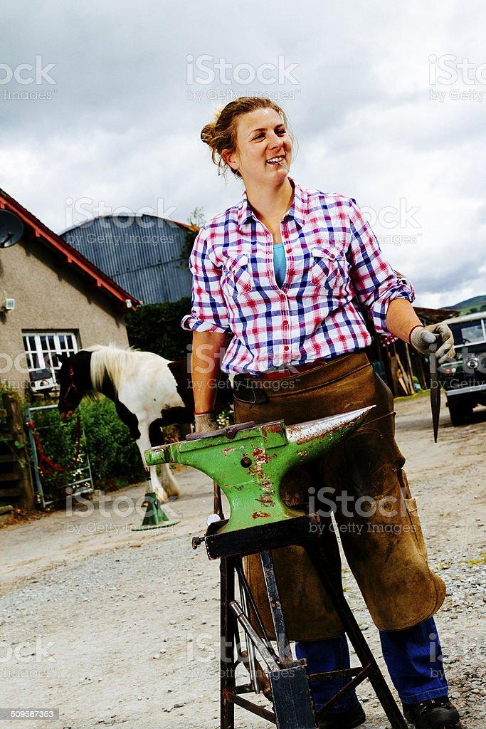 Female farrier at work beside anvil stock photo