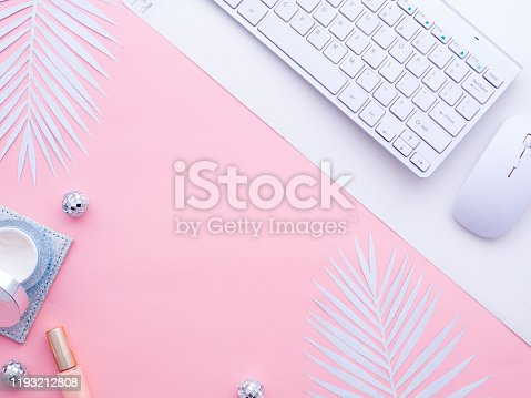 Female fashion beauty blogger home office workspace. Computer keyboard, cosmetics, creams nail polishe bottles, mouse, Christmas balls on pink color background with white fern leaf. Top view