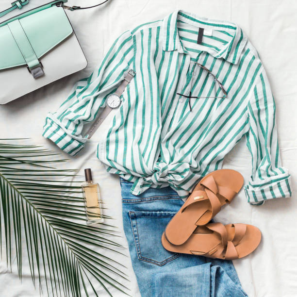 Female fashion clothes flat lay, square Feminine summer fashion composition: striped blouse, slippers, bag, sunglasses, watch, perfume, jeans, palm leaf on white background. Flat lay, top view clothes. Female fashion blog or social media clothing stock pictures, royalty-free photos & images