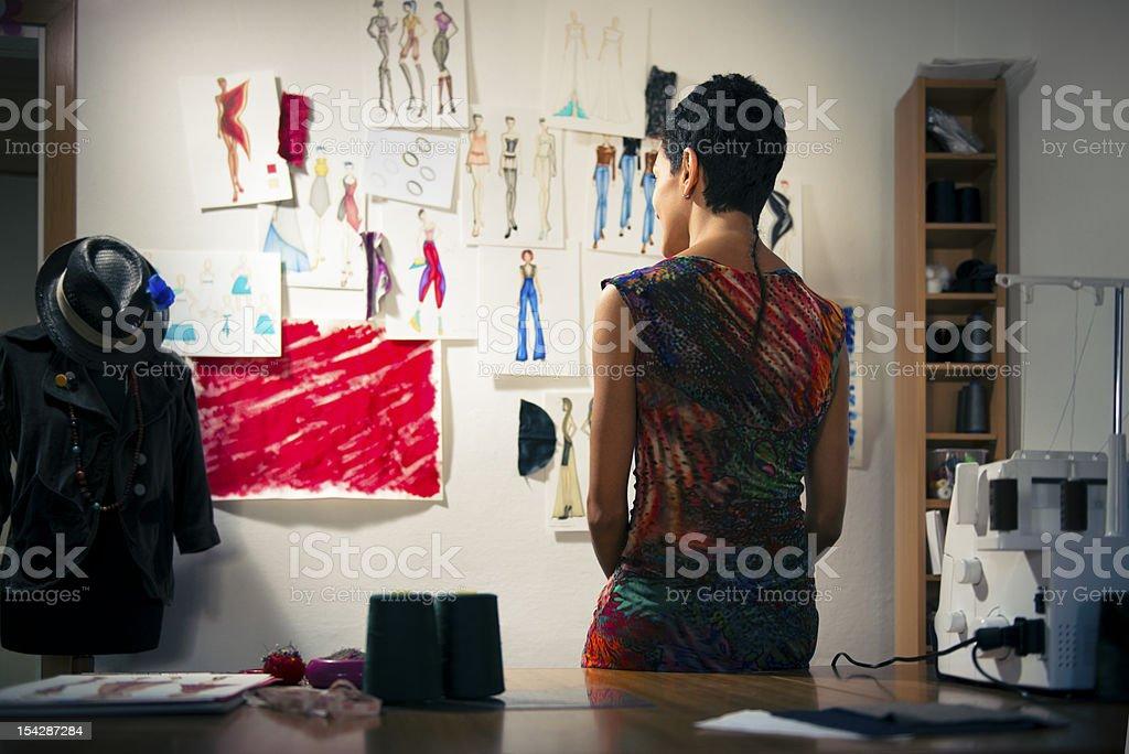 Female fashion designer contemplating drawings in studio stock photo