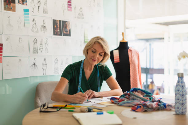 Female fashion designer drawing a sketch on a table stock photo