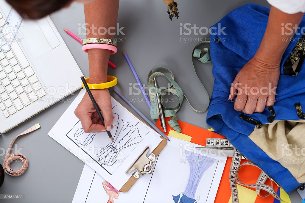 Female fashion designer hands holding drawing pad and pen stock photo