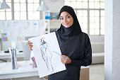 Arab female designer holding a sketch with new model, looking at camera.