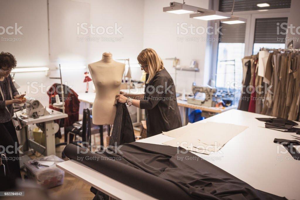 Female fashion designer with assistance in fashion design studio stock photo