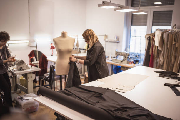 weibliche mode-designer mit hilfe in mode-design-studio - nähpuppen stock-fotos und bilder