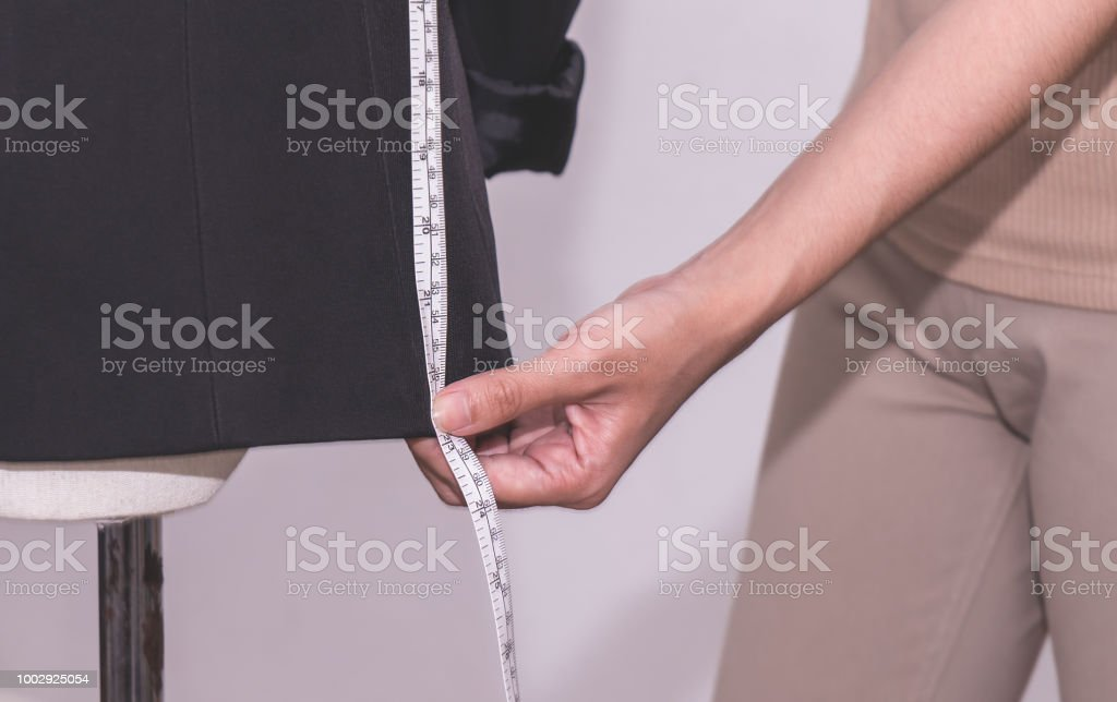 Female fashion tailor is measuring office suit jacket stock photo