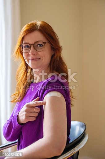 Woman looking at camera pointing at her arm with a bandage after getting the covid-19 vaccine. Female feeling proud after getting coronavirus vaccine at vaccination center.