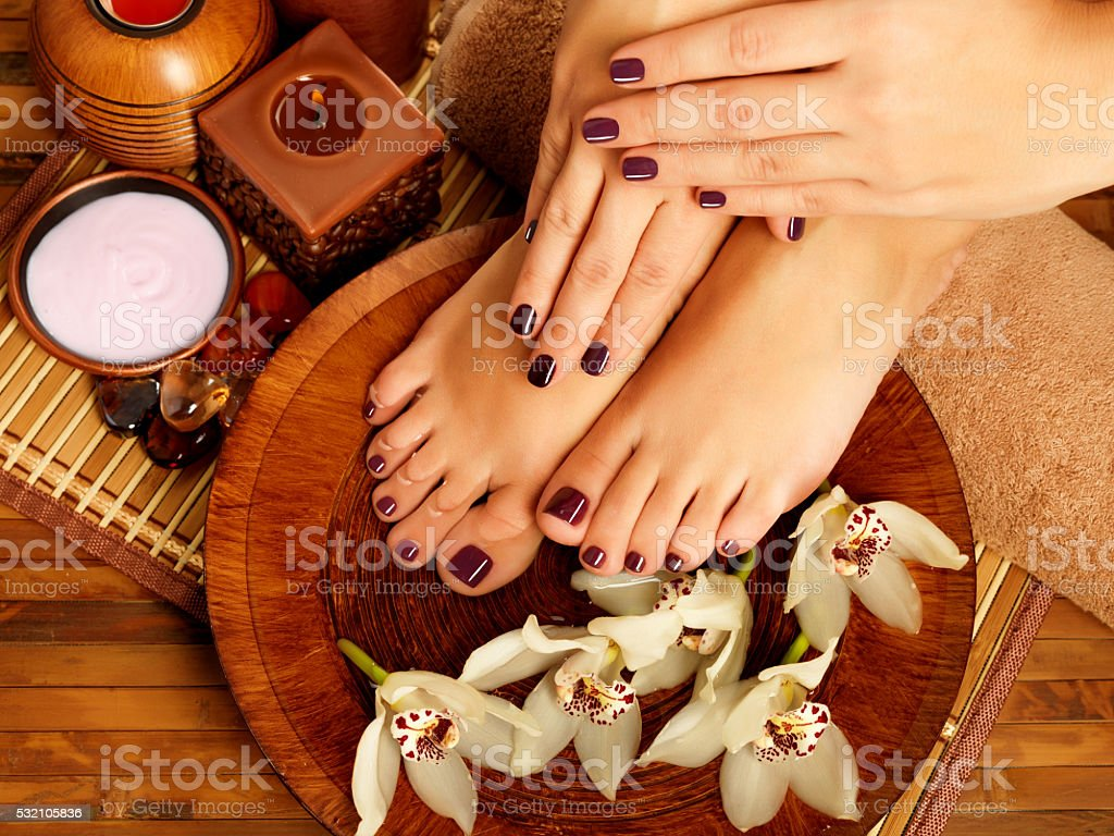 female feet at spa salon on pedicure procedure stock photo