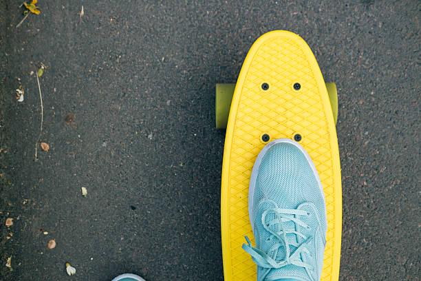 Femelle pieds dans les chaussures de tennis bleus sur un skate - Photo