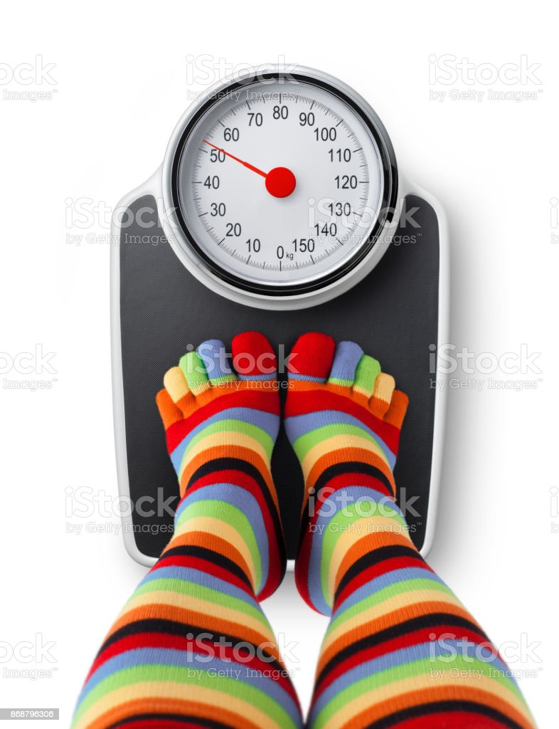 Female feet in colorful socks stepping on bathroom scales. stock photo