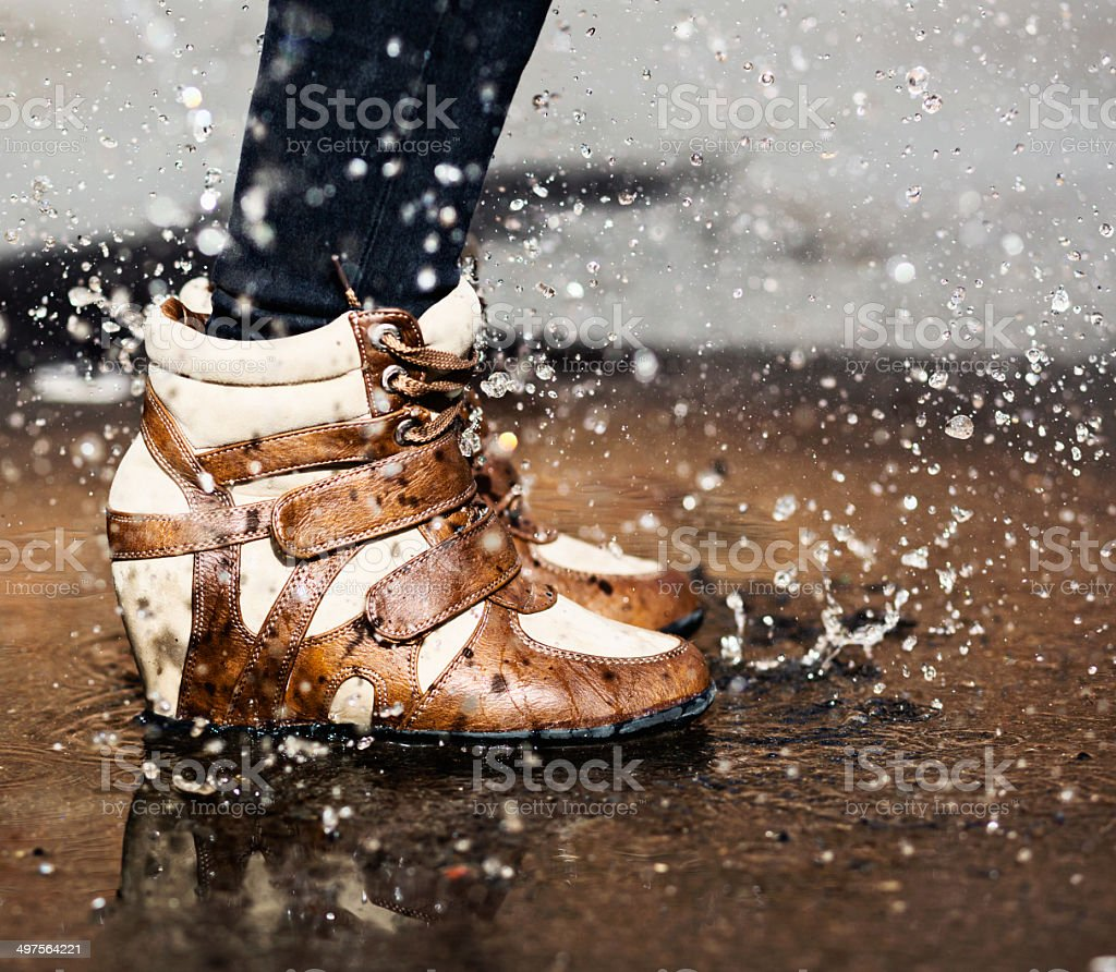 Female feet in fashionable wedge-heel boots stamp in puddle playfully stock photo