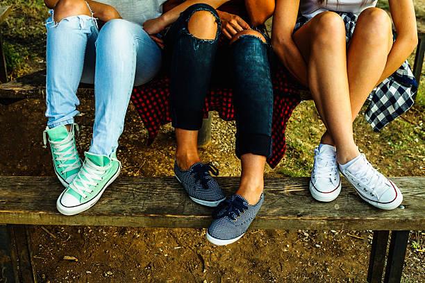weibliche füße in jeans und sportschuhe auf einer bank - sitzbank schuhe stock-fotos und bilder