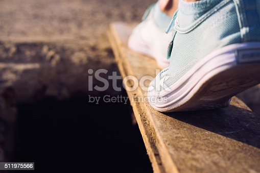 Female feet in sneakers walking on a narrow board above a large pit. Low-angle shooting, close-up.