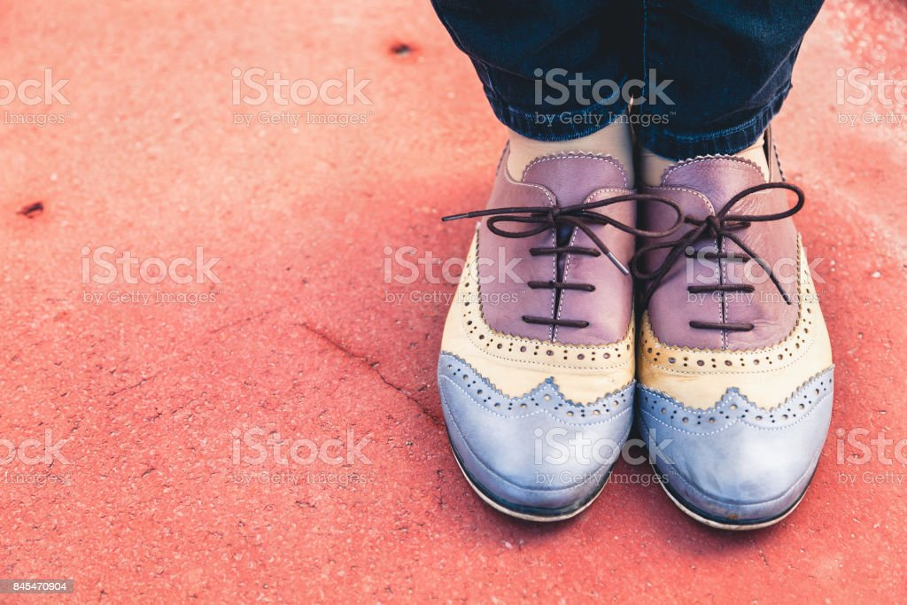 Female feet in stylish shoes brogues on brown surface stock photo