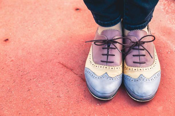 weibliche füße in stilvolle schuhe halbschuhe auf braunem untergrund - budapester schuhe stock-fotos und bilder