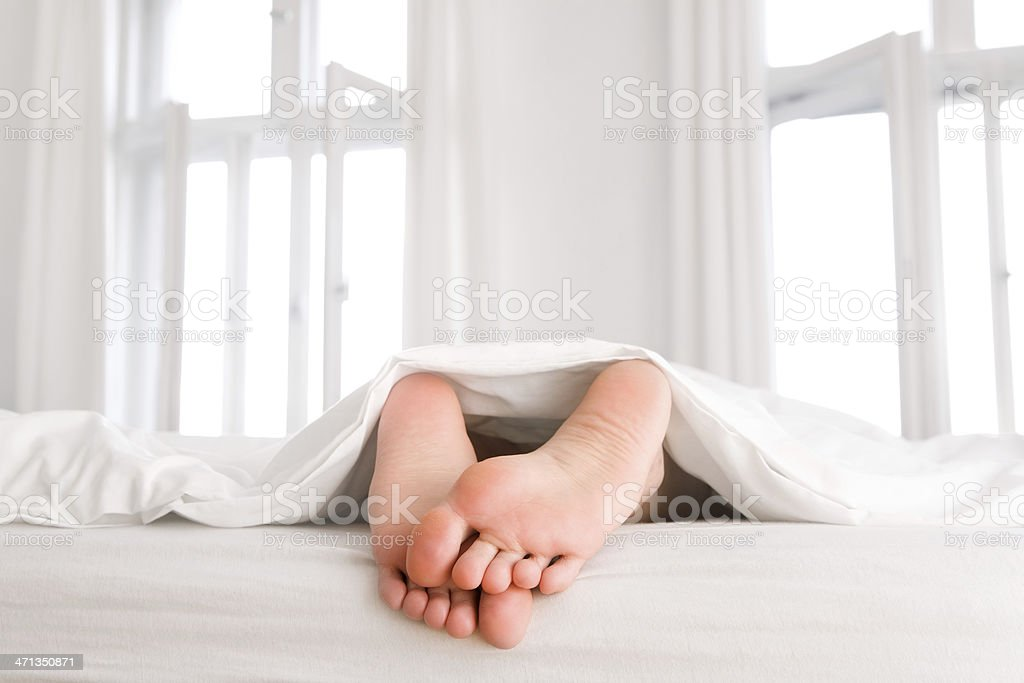 Female feet looking out the blanket royalty-free stock photo