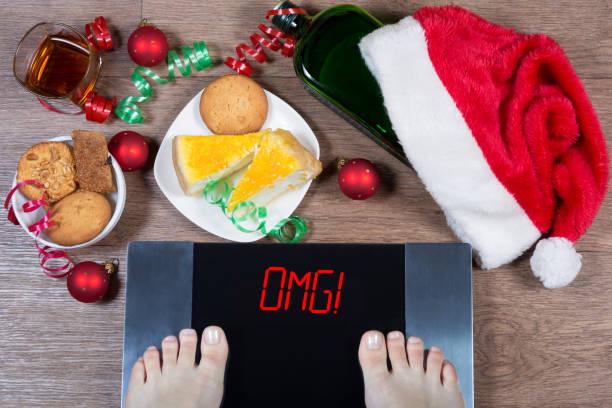 """weibliche füße auf digitalwaage mit schild """"omg!"""" umgeben von weihnachtsschmuck, flasche, glas alkohol und süßigkeiten. folgen von überessen und ungesunde lifestyle während der ferien. - fett nährstoff stock-fotos und bilder"""