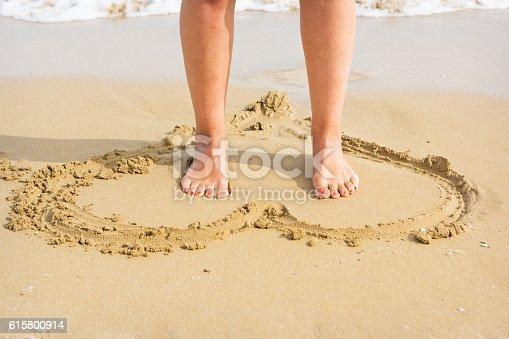 Female feet with red nail polish on drawn heart in yellow sandy beach. Shot taken on beautiful beach near Siracusa, Italia