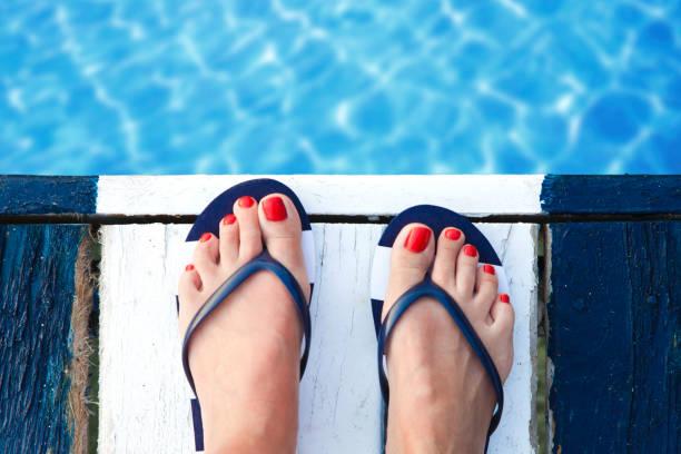 weibliche füße auf steg - salzwasser sandalen stock-fotos und bilder