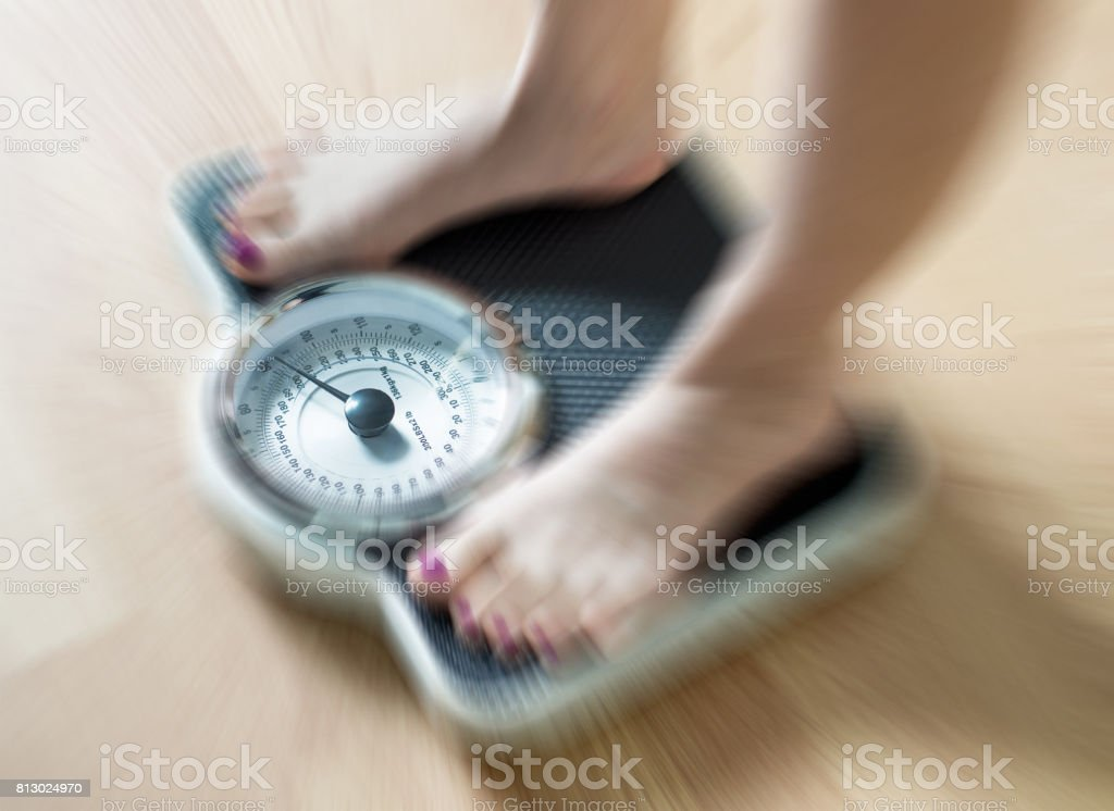 Female feet on scale with dramatic blur zoom effect. stock photo