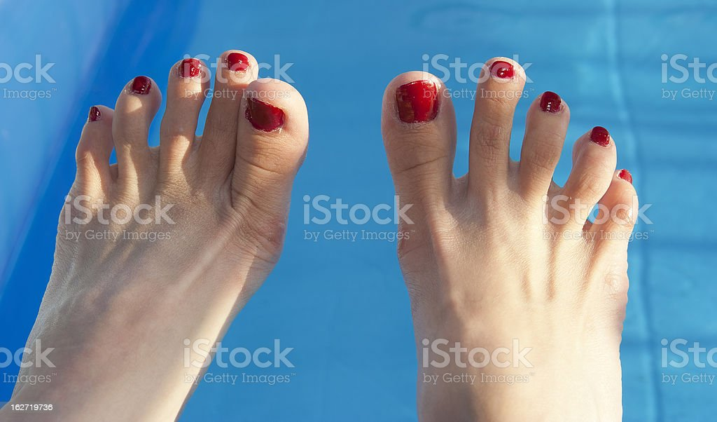 Female feet on the pool, detail stock photo