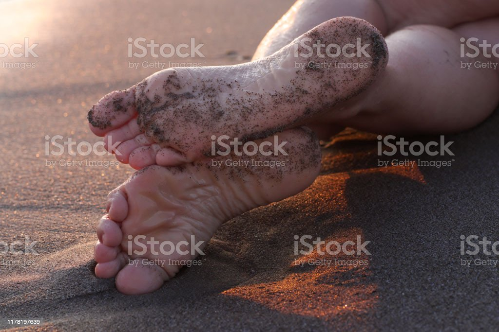 Female feet on the sand at sunset - Foto stock royalty-free di Adulto