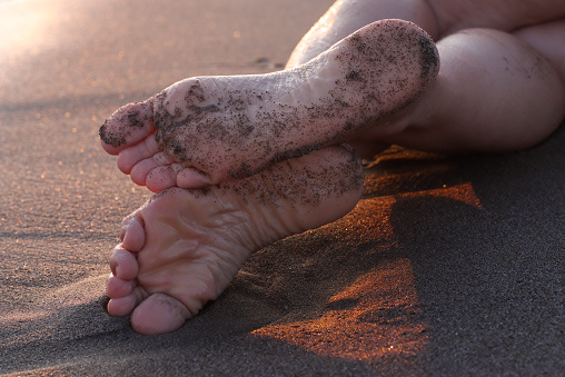 Female Feet On The Sand At Sunset - Fotografie stock e altre immagini di Adulto